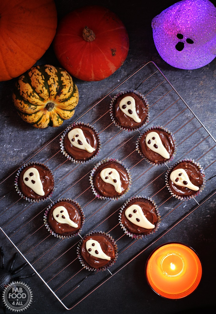 Easy Halloween Ghost Cupcakes - delicious chocolate & coffee flavoured sponge topped with chocolate spread & a handmade white chocolate ghost. Ghost, candle and pumpkin background.