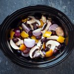 Chicken thighs, red onion, chestnut mushroom & yellow peppers in slow cooker.