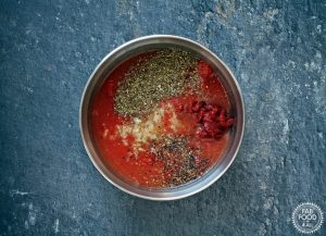 Chicken stock, tinned tomatoes, garlic, herbs, tomato puree etc in a bowl.