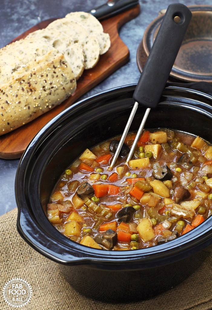 Easy Slow Cooker Vegan Stew - a hearty, tangy stew with root vegetables, Chestnut mushrooms & peas. Serve with crusty bread to mop up the cooking juices! #slowcooker #crockpot