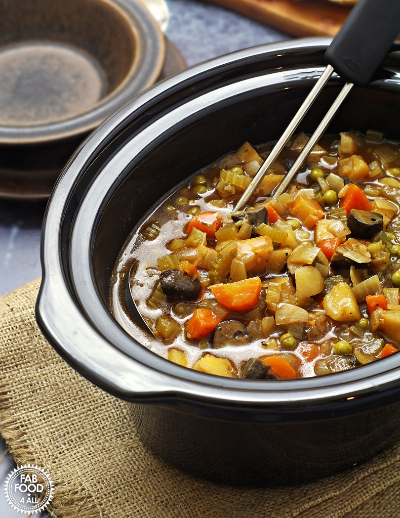 Easy Slow Cooker Vegan Stew - a hearty, tangy stew with root vegetables, Chestnut mushrooms & peas. Serve with crusty bread to mop up the cooking juices! #slowcooker