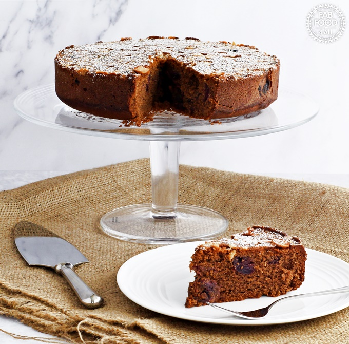 Simple Cherry Chocolate Cake on a glass pedestal with silver cake server plus slice of cake on a plate.