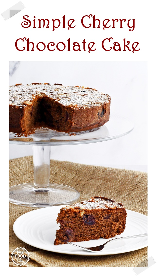 Simple Cherry Chocolate Cake on a glass pedestal with silver cake server.