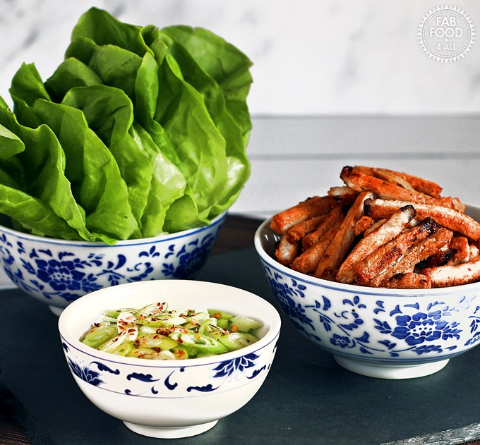 Korean BBQ Style Spicy Pork Lettuce Wraps - stripes of marinated pork on lettuce leaves, garnished with spring onion & served with sweet chilli sauce and soy sauce.
