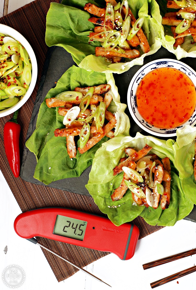 Korean BBQ Style Spicy Pork Lettuce Wraps - stripes of marinated pork on lettuce leaves, garnished with spring onion & served with sweet chilli sauce and soy sauce. Thermapen Professional digital thermometer also displayed.