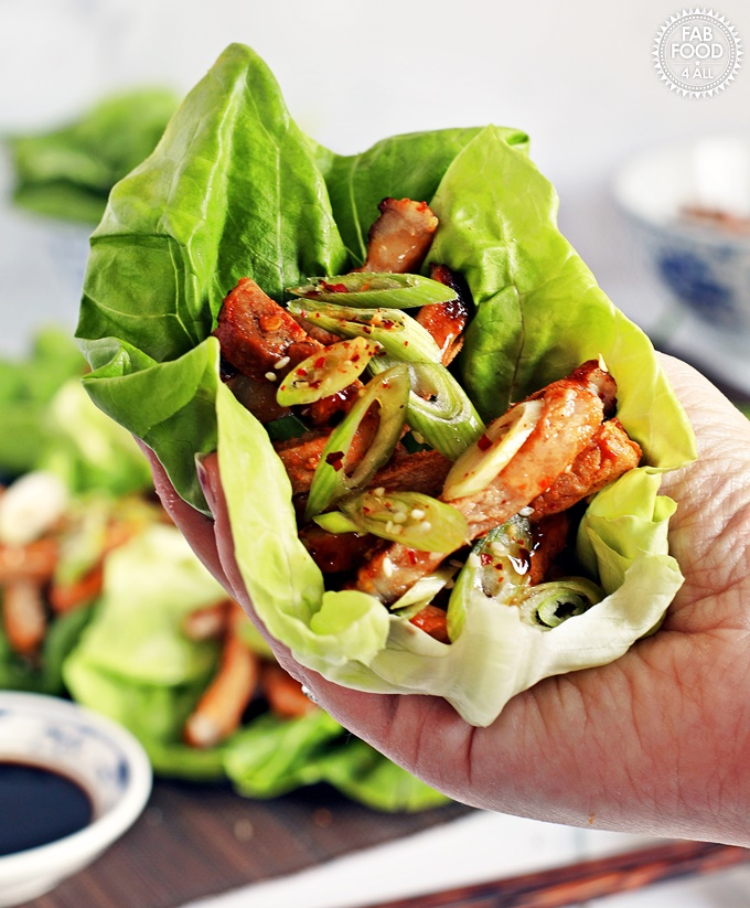 Korean BBQ Style Spicy Pork Lettuce Wraps - stripes of marinated pork on lettuce leaves, garnished with spring onion & served with sweet chilli sauce and soy sauce. Held up to camera in hand.