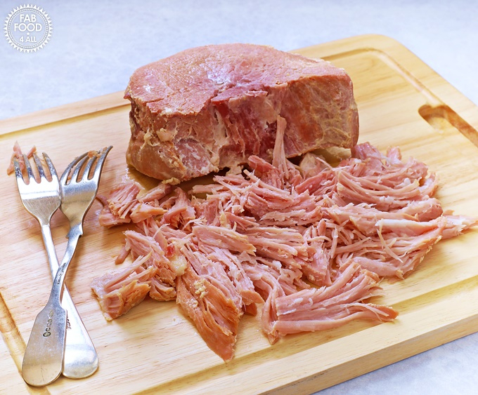 2 Ingredient Pulled Slow Cooker Gammon (Shredded Ham) on a board. with 2 forks