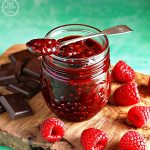 Jar of Raspberry & Chocolate Jam on a wooden board with dark chocolate & raspberries.