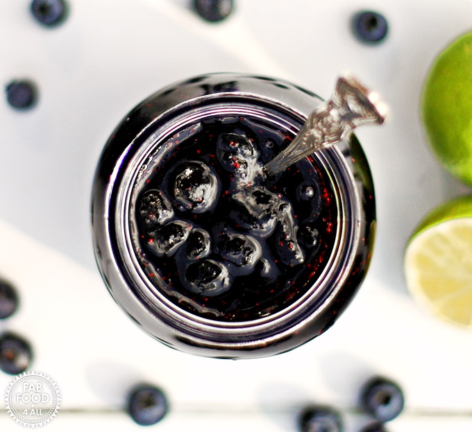 Blueberry & Lime Jam aerial view with jam spoon looking into jam jar.