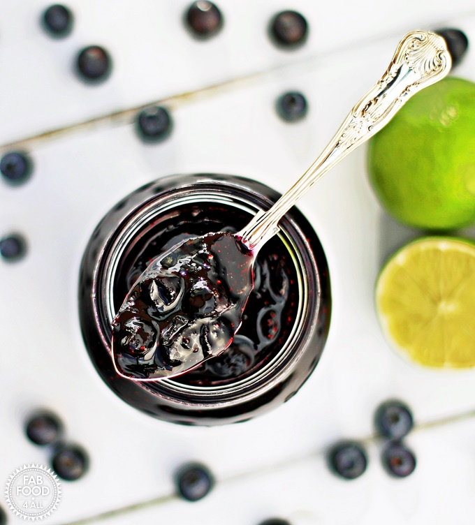 Blueberry & Lime Jam in a jar surrounded by blueberries & limes.