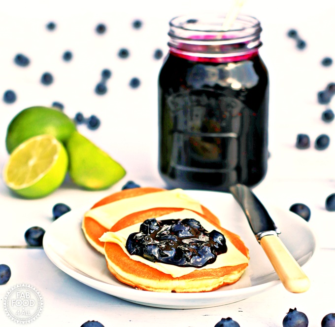 Jar or Blueberry & Lime Jam with a plate of scotch pancakes.