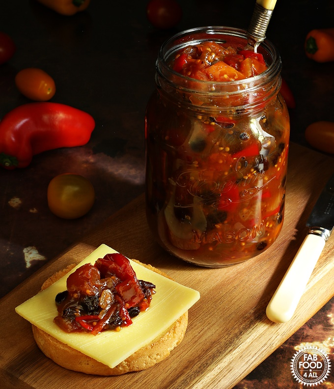 Spicy Baby Tomato & Sweet Pepper Chutney in a jar with fork in it plus cheddar cheese on cracker.