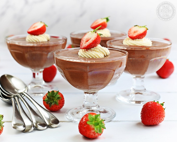 Foolproof Rich Chocolate Mousse with piped whipped cream & strawberry decoration in sundae glasses.