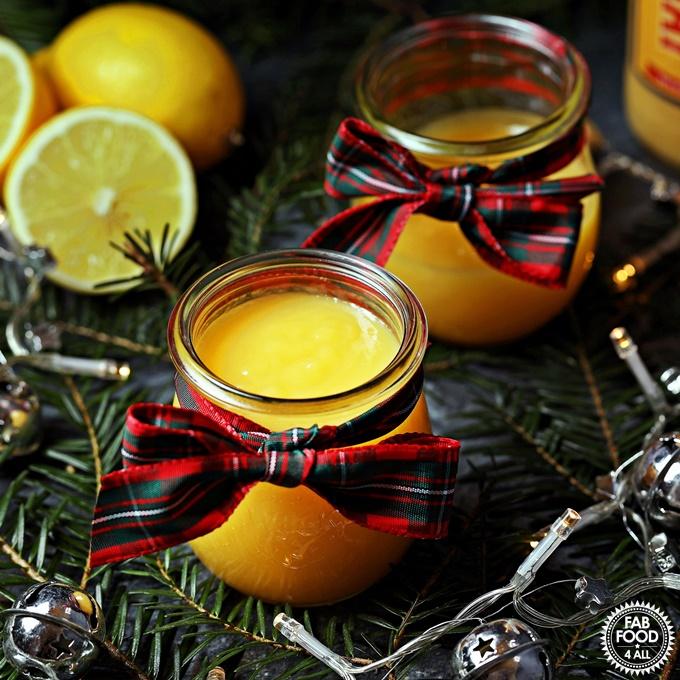 Advocaat & Lemon Curd with teaspoon, lemons, Christmas tree branches & fairy lights.