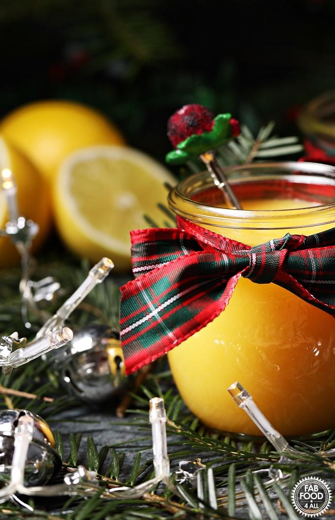 Snowball (Eggnog) Curd in jar with tartan bow with teaspoon, lemons, Christmas tree branches & fairy lights.