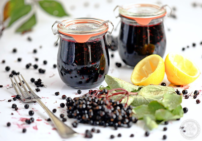 Elderberry Jam jars with blueberries and lemon halves.