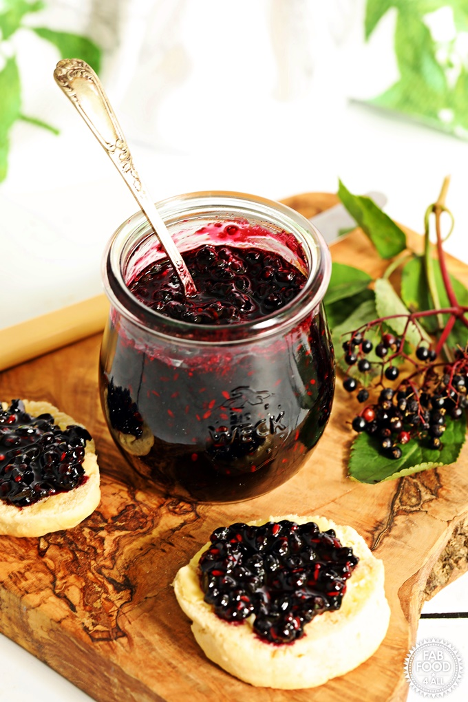 Elderberry Jam with teaspoon on board with scones.