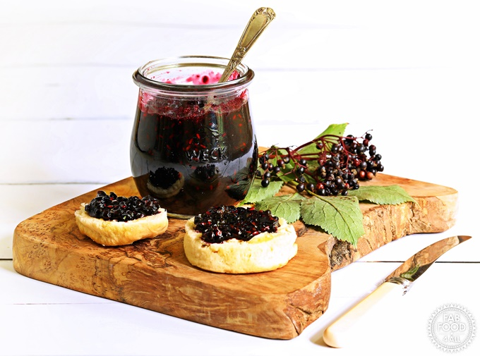 Blueberry Jam in jar with teaspoon submerged on a board with scones.