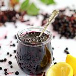 Blueberry Jam in jar with teaspoon submerged, surrounded by blueberries & lemon rinds.