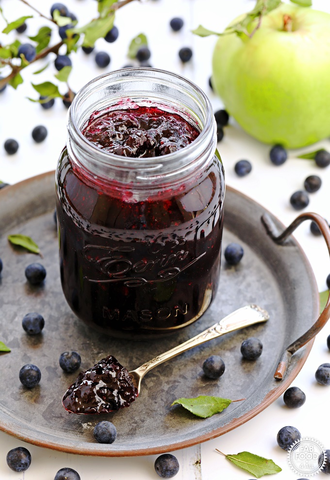 Sloe & Apple Jam in a jar on plate with spoonful of jam.
