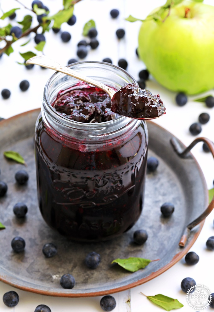Sloe & Apple Jam in a jar on plate with spoonful of jam resting on jar.