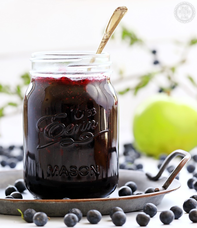 Sloe & Apple Jam in a jar on plate with spoon in jar and apple in background.