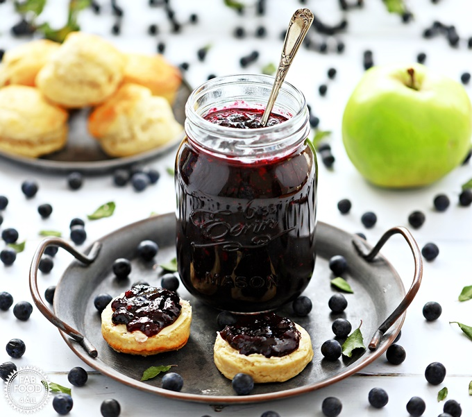 Sloe & Apple Jam in a jar on plate with spoon in jar, scones and apple in background.