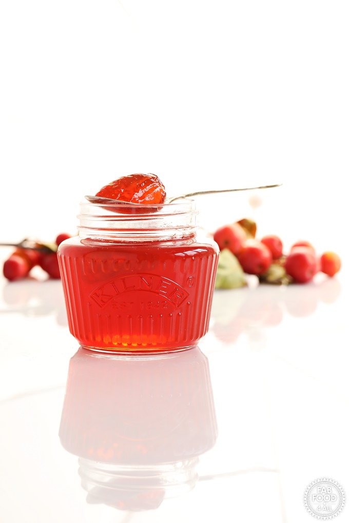 Side shot of Easy Crab Apple Jelly in a jar with spoon resting on top.