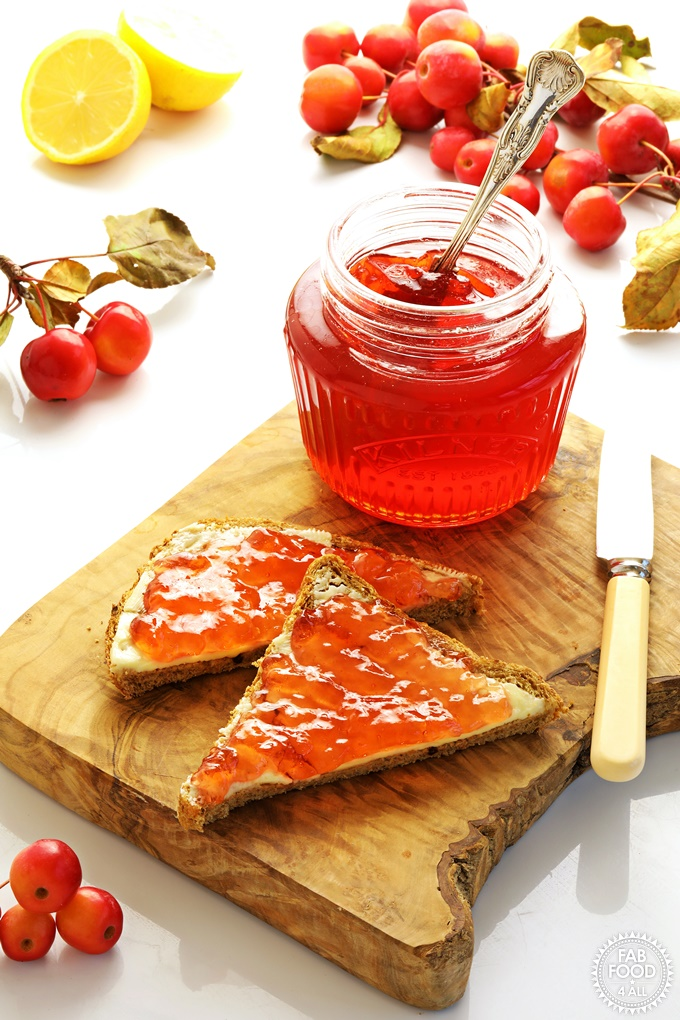 Jar of Crab Apple Jelly with it spread on bread and butter.