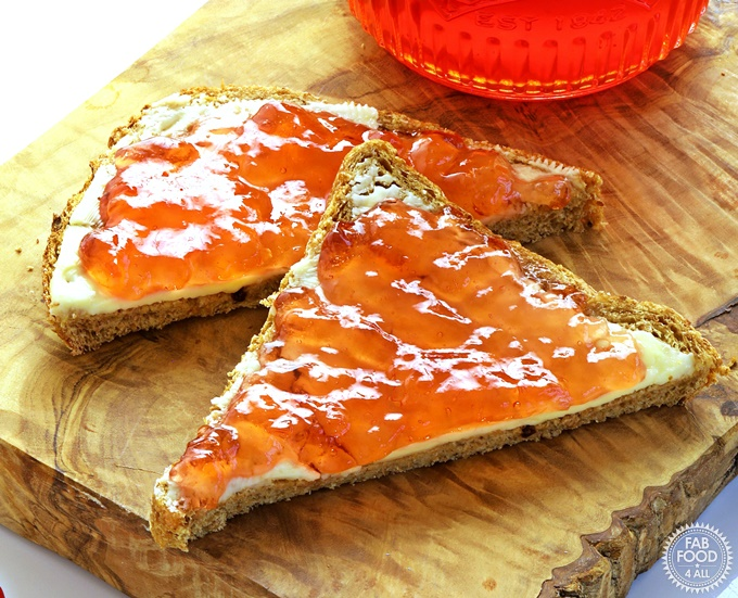 Easy Crab Apple Jelly on bread and butter on a wooden board.