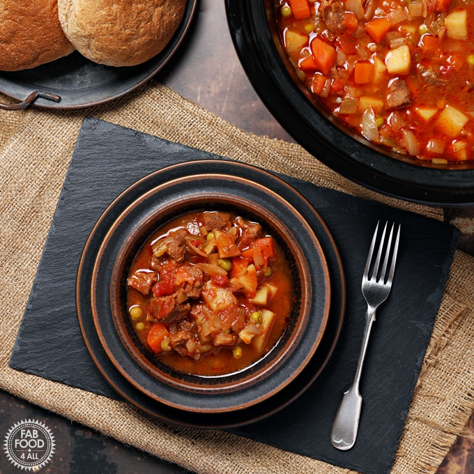 Slow Cooker Beef Stew in a bowl. with rolls & slow cooker.