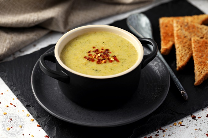 Broccoli & Cheddar Soup in a bowl with spoon & toast on a slate mat.