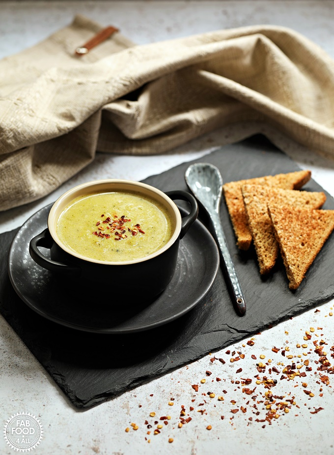 Broccoli & Cheddar Soup in a bowl with spoon & toast on a slate.