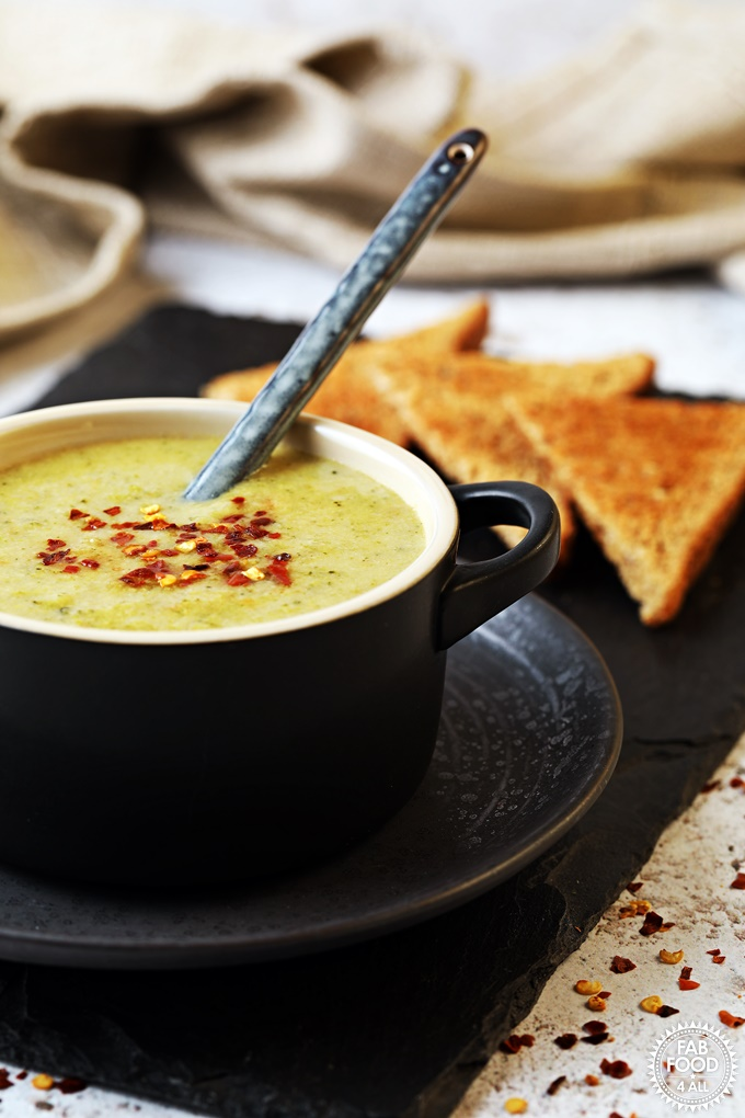 Broccoli Cheddar Soup in a bowl with spoon & toast on a slate.