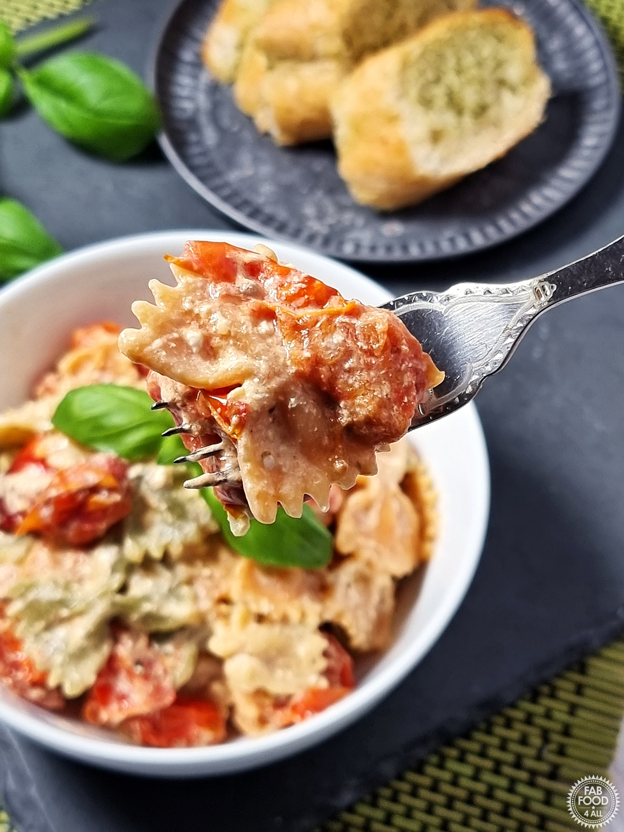 Best Baked Feta Pasta Recipe on a fork with bowlful in background.