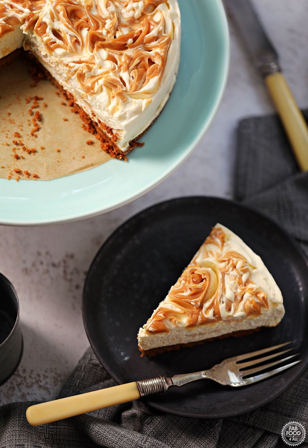 Slice of Easy Salted Caramel Cheesecake on a plate with whole cheesecake in background. (aerial view)