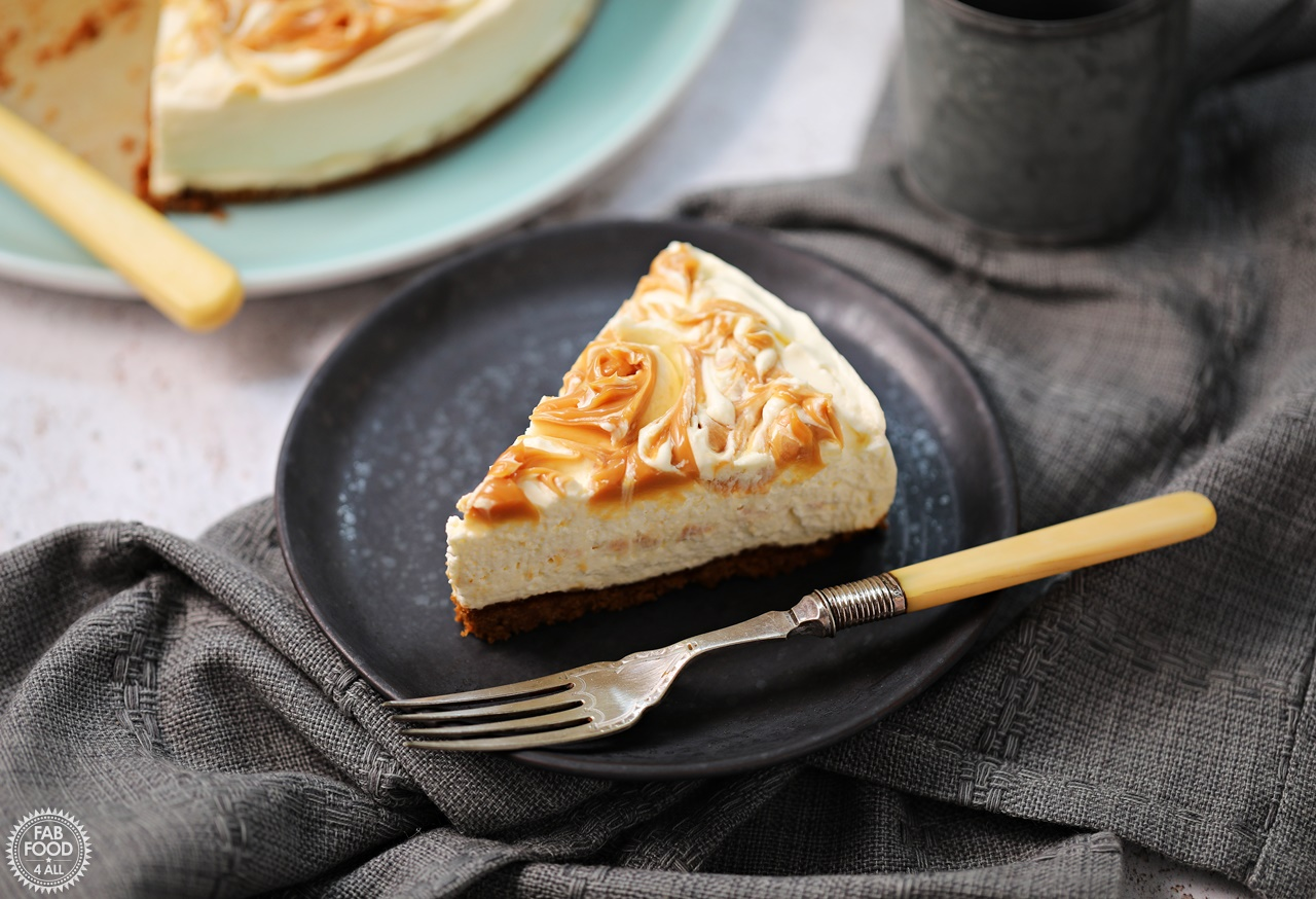 Slice of Easy Salted Caramel Cheesecake on a plate with whole cheesecake in background.