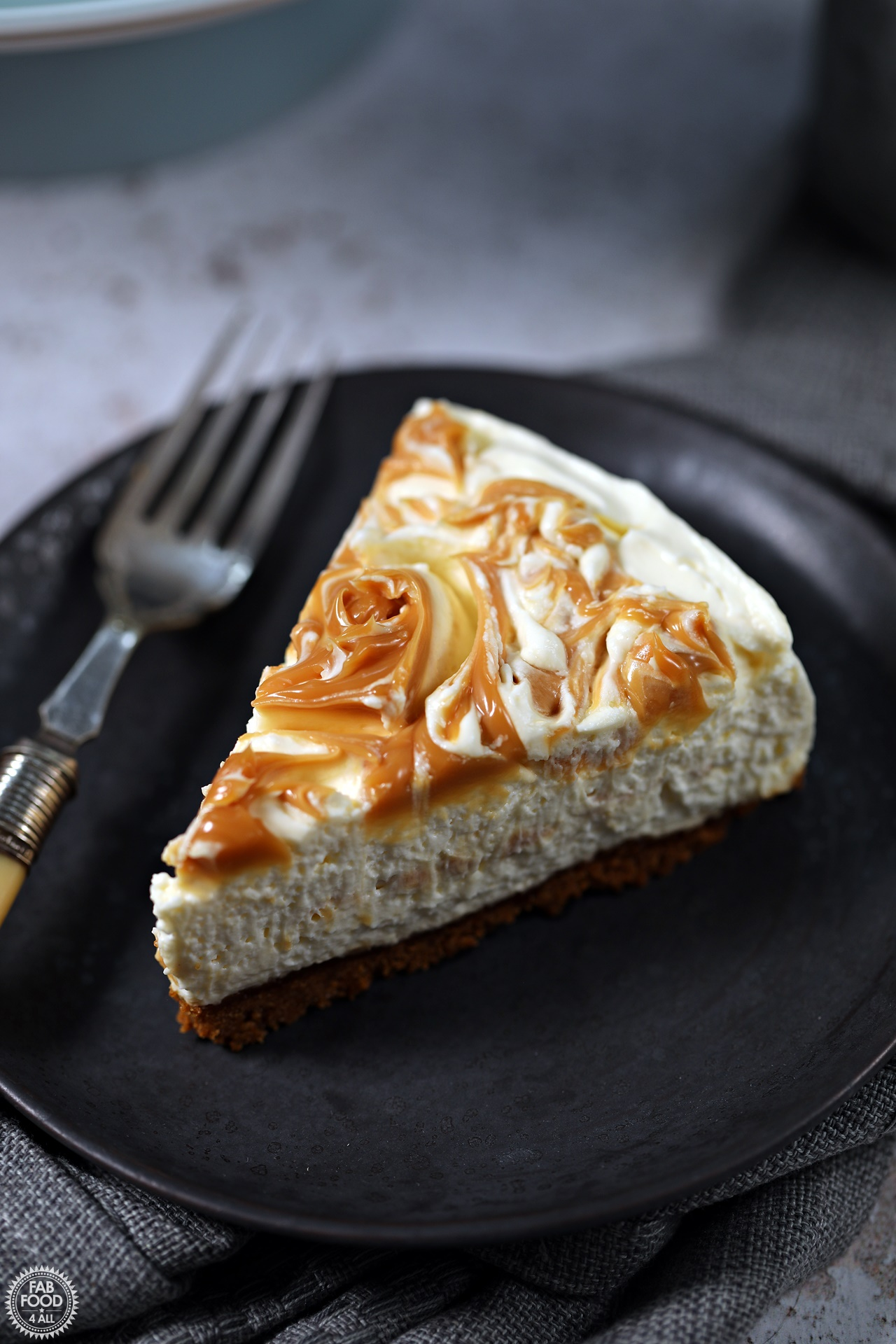 Slice of Easy Salted Caramel Cheesecake on a plate with fork.