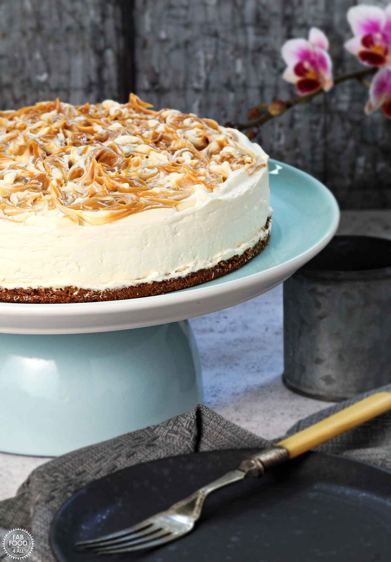 Salted Caramel Cheesecake no bake on a blue pedestal with plate and cup.