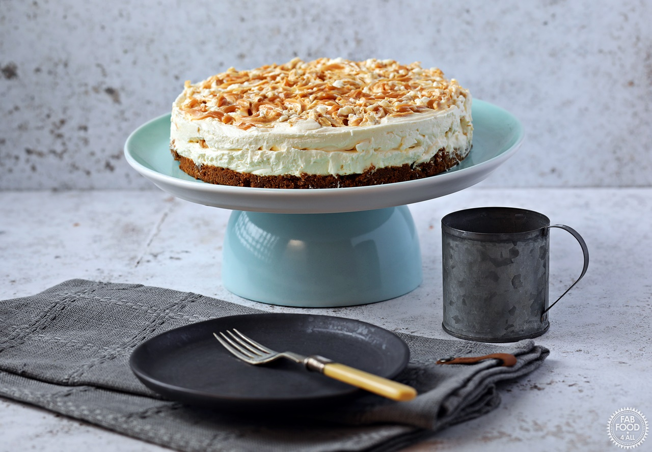 Salted Caramel Cheesecake (no bake) on a pedestal with plate & cup.