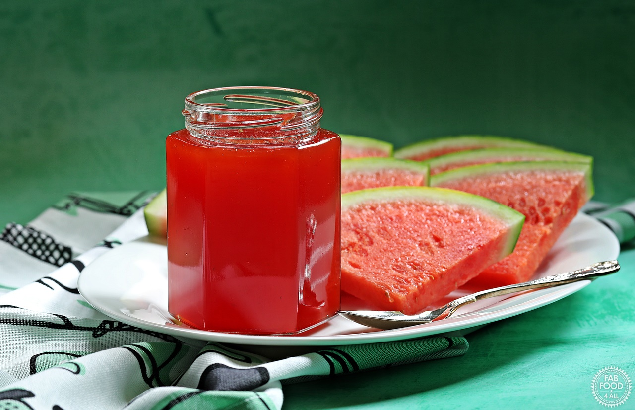 Slices of watermelon & a jar of watermelon jam on a platter.
