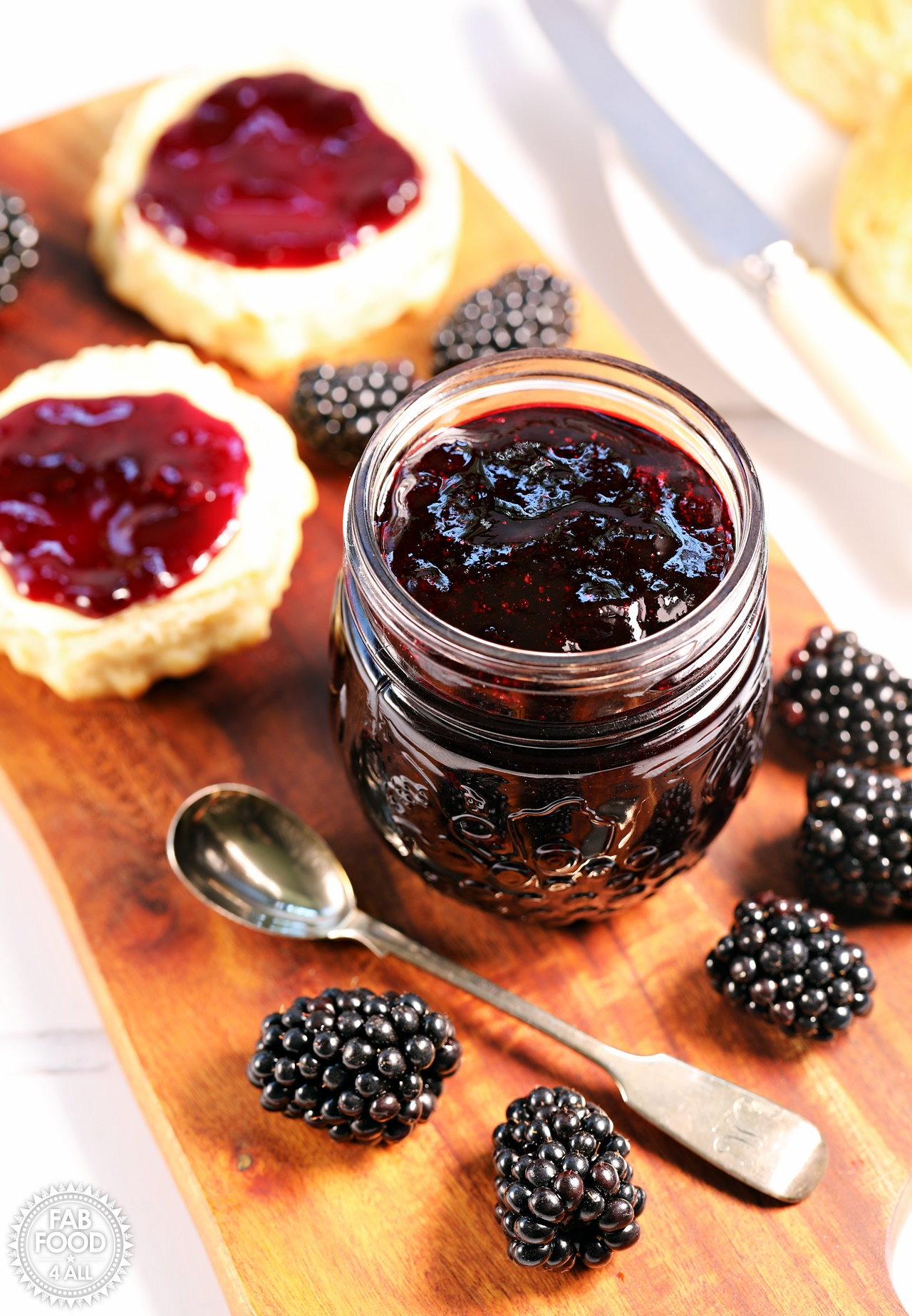 Easy Seedless Blackberry Jam with scone. and blackberries on a board.